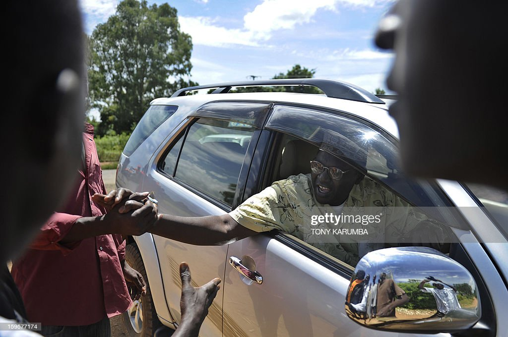 President Barack Obama's Kenyan half brother, Malik Obama greets supporters January 16, 2013 near Nyang'oma in Kogelo, now renowned as the Obama's traditional home. Malik has launched his own political career by announcing his intention to run for a Kenyan gubernatorial seat in the upcoming March 4 general elections. Malik, 54, who shares a father with the US president told AFP that the achievements of his more famous half brother have 'inspired and challenged' him to get into active politics in his homeland. The trained economist said he is the right candidate to deal with the 'endless cycle of poverty and unemployment that bedevils my people.' . AFP PHOTO/Tony KARUMBA