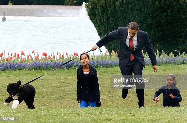 S President Barack Obama's new Portuguese water dog Bo pulls away as Obama walks with daughters Malia and Sasha on the South Lawn of the White House...