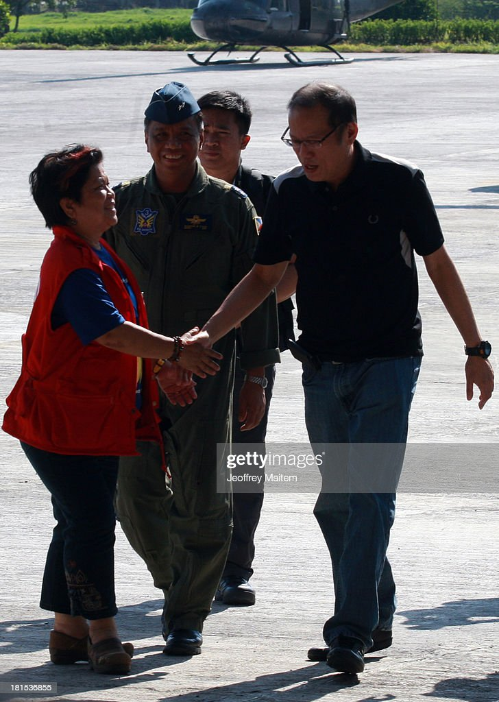 President Benigno Aquino III shake hands with Secretary Dinky Soliman of Department of Social Welfare and Development minutes before he departs for Manila from Zamboanga, Philippines as the fighting involving soldiers and Muslim rebels subsides on September 22, 2013. Rebellion and violation of international humanitarian laws have been filed against rebel chieftain Nur Misuari, the leader and founder of the Moro National Liberation Front, his top aide, Habier Malik and undetermined number of John Does and Jane Does who remain at large. The President said the military and police will continue to pursue the whereabouts of Misuari and Malik, believed to be still holding between 20 and 30 civilian hostages. The fighting that started September 9, 2013 came weeks after Misuari declared an independence of Mindanao. His group signed a peace accord with government in 1996.