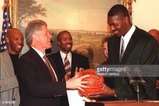 President Bill Clinton accepts a basketball from Houston Rockets' Hakeem Olajuwon 18 February at the White House in Washington The Houston Rockets...