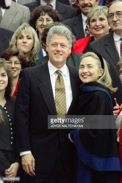 US President Bill Clinton and First Lady Hillary Clinton pose at the White House on December 3 1995 with some of the volunteers who decorated the...
