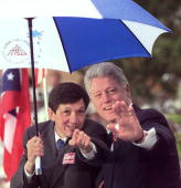 President Bill Clinton and former Cleveland Mayor Dennis J Kucinich wave to someone they spotted in the crowd 21 October just before the president's...