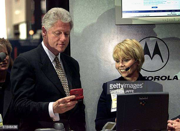 President Bill Clinton and Janice Webb a senior vice president with Motorola inspect a twoway pager at the COMDEX/Spring 2000 a major information...