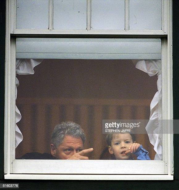 President Bill Clinton and nephew Tyler Clinton look out from a second story window of his birthplace after a dedication ceremony 12 March in Hope...