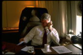 President Bill Clinton at his desk aboard Air Force One talking on the telephone to Transportation Secretary Rodney Slater about Amtrak strike...