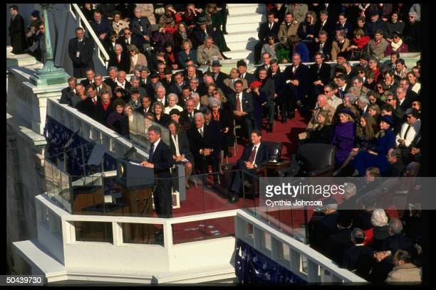 President Bill Clinton delivering his inaugural speech framed by family members the Gore family and a host of political notables January 20 1993