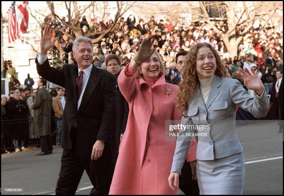 US President Bill Clinton First Lady Hillary and daughter Chelsea wave to the crowd as they walk the inaugural parade route 20 January in Washington...