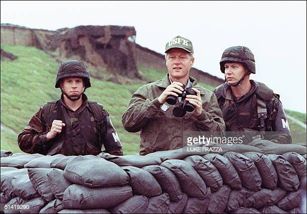 President Bill Clinton in a picture taken 11 July 1993 uses binoculars to look across the Demilitarized Zone into North Korea with two US soldiers...