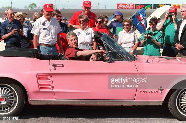 President Bill Clinton in a picture taken 17 April 1994 in Charlotte sits in a 'Playboy Pink' colored 1967 Ford Mustang owned by Bob and Rochelle...
