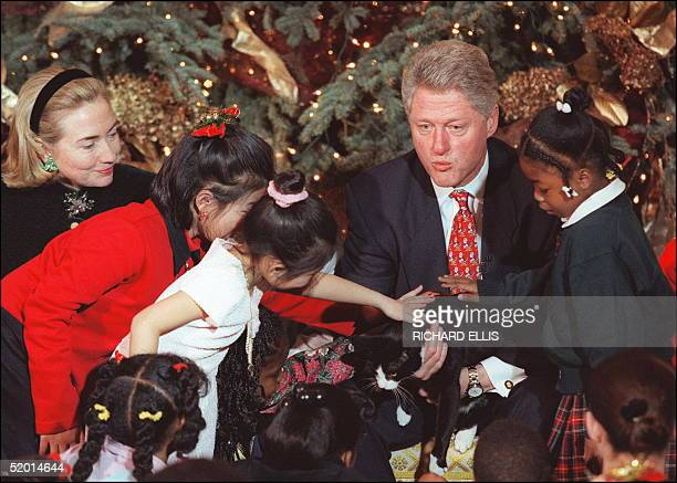 President Bill Clinton in picture taken 20 December 1996 at the White House in Washington DC holds Socks the cat for children to pet as his wife...