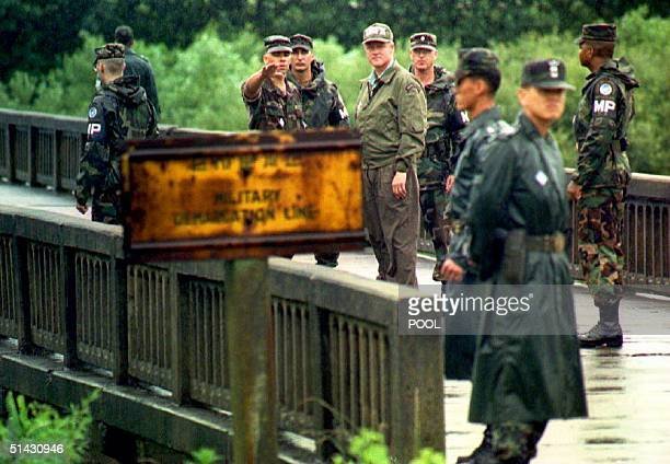 S President Bill Clinton is escorted by Military Police as a US Army officer describes 11 July 1993 the Bridge of No Return separating North and...