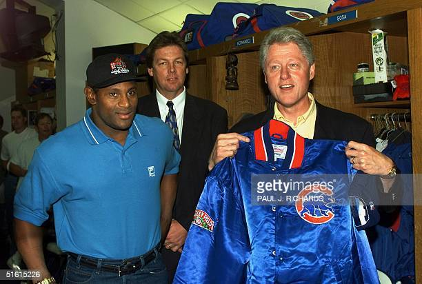 President Bill Clinton is presented with a Chicago Cubs jacket by Cubs player Sammy Sosa as Cubs General Manager Ed Lynch looks on in the Cubs locker...