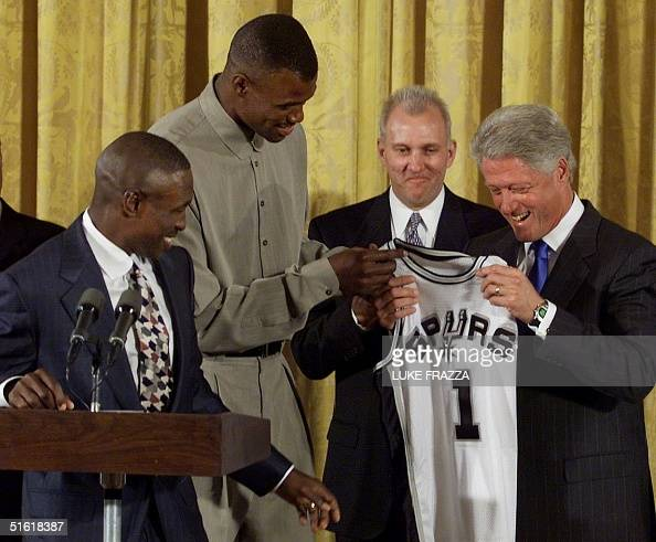 President Bill Clinton is presented with a San Antonio Spurs team jersey 07 September by Spurs players David Robinson and Avery Johnson as coach...