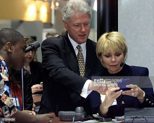 President Bill Clinton Janice Webb a senior vice president with Motorola and student Jason Bell inspect a twoway pager at the COMDEX/Spring 2000 a...