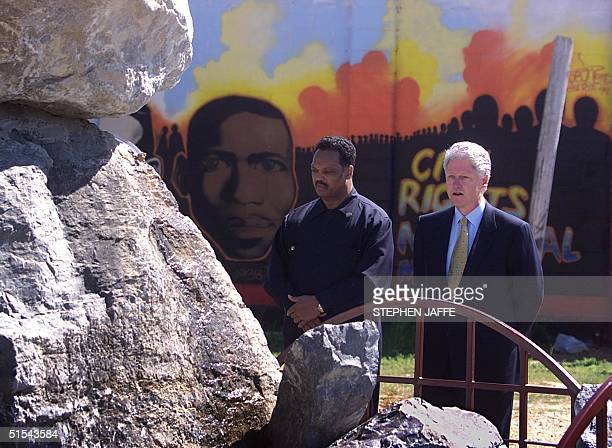 President Bill Clinton joined by Reverend Jesse Jackson look at a monument of rocks to commemorate 'Bloody Sunday' prior to leading the reeactment of...