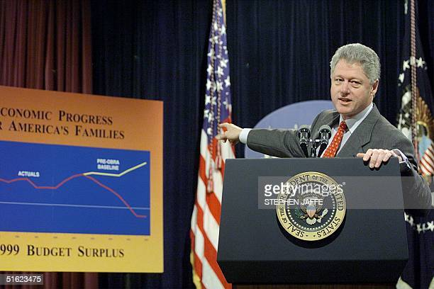 President Bill Clinton points to a chart during the announcment of the 76 USD billion budget surplus for fiscal year 1999 at the Old Executive Office...