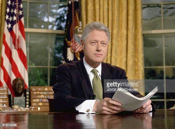 President Bill Clinton poses for photographs after addressing the nation from the Oval Office in the White House 10 June following the end of...