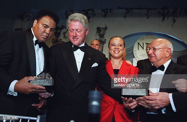 President Bill Clinton presents former world boxing heavyweight champion Muhammad Ali and his trainer Angelo Dundee with the National Italian...