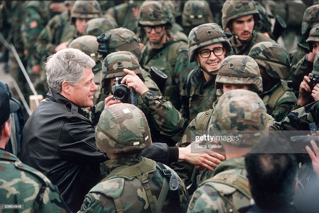 President Bill Clinton reaching to shake hands in crowd of US soldiers, visiting troops on peacekeeping mission, enforcing US-brokered peace accord in civil war-torn former Yugoslav republic.