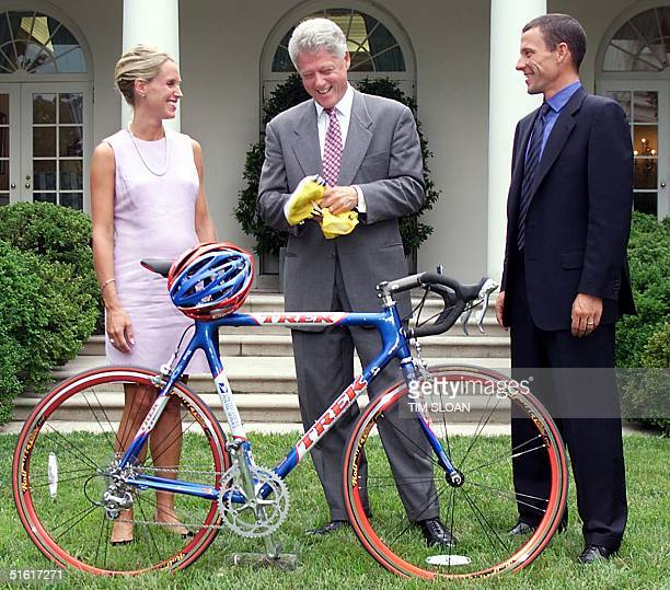 President Bill Clinton receives a replica bicycle helmet and autographed jersey from1999 Tour De France champion Lance Armstrong and his wife Kristen...