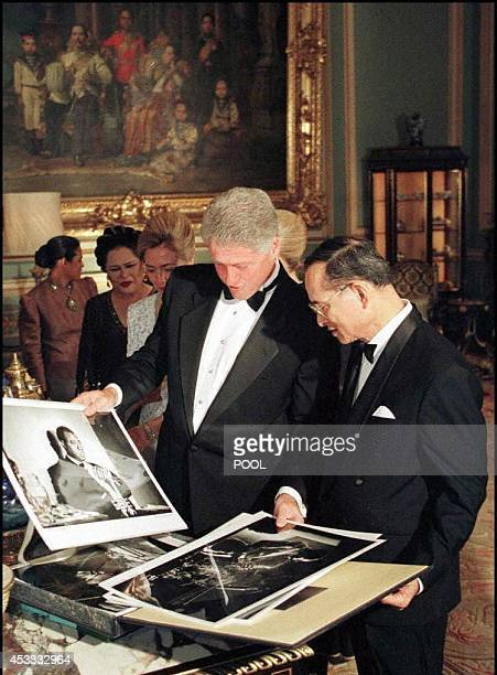 US President Bill Clinton shows pictures of famous American jazz musicians to Thai King Bhumibol Adulyadej as an exchange gifts at the Grand Palace...