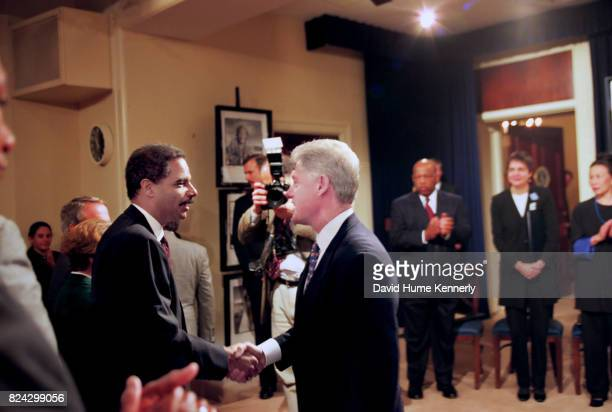 President Bill Clinton speaks with Eric Holder his deputy Attorney General at the 50th anniversary of the adoption of the Universal Declaration of...