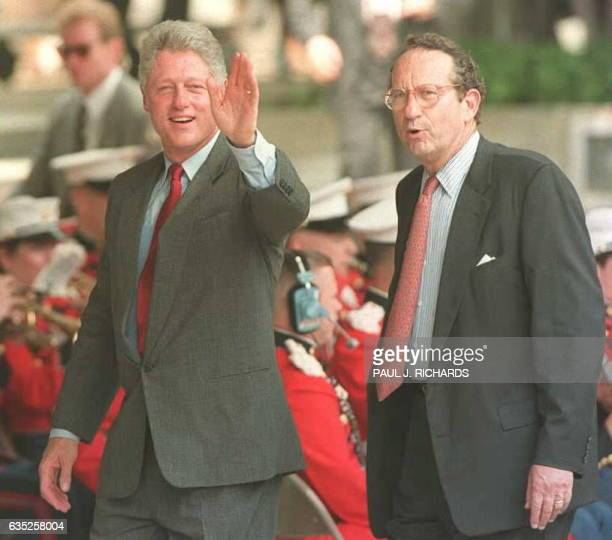 US President Bill Clinton waves to photographers as he walks with John Deutch director of the CIA during ceremonies at CIA Headquarters in Langley VA...