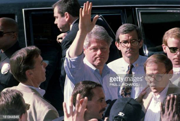 US President Bill Clinton waves to residents 19 January 1994 during a tour of earthquake stricken areas near Los Angeles CA Clinton toured damaged...