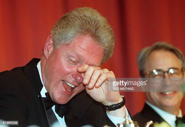 President Bill Clinton wipes away tears of laughter as he and White House Correspondents' Association President Carl P Leubsdorf listen to comedian...