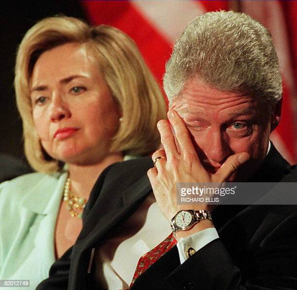 President Bill Clinton wipes his eyes as his wife HIllary looks on during a memorial service at the Commerce Department marking the one year...