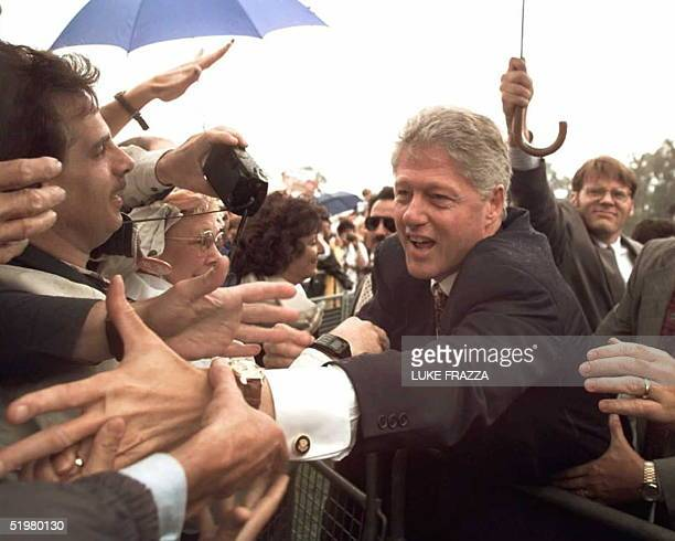 President Bill Clinton works the crowd after giving a speech at a rainy rally 17 September at John Glenn High School in Westland Michigan Clinton...