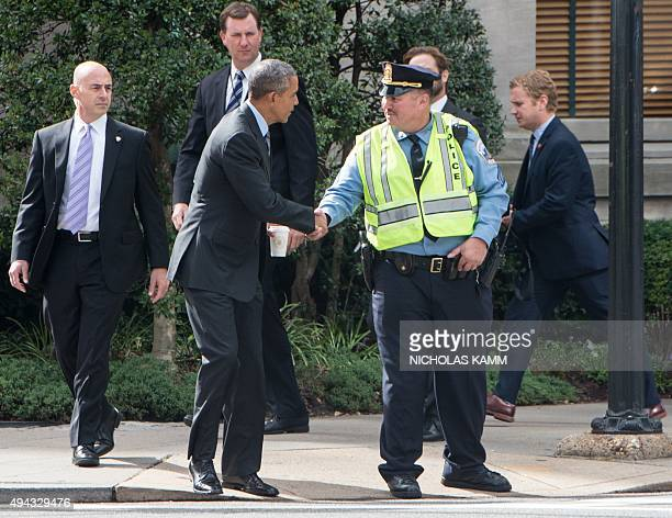 US President Brarck Obama greets a police officer as he walks back to the White House after having lunch with former senators Tom Daschle and George...