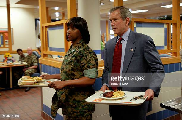 President Bush joins Staff Sgt Angela Austin as they prepare to have lunch at the mess hall at Camp Lejeune After addressing Marines Bush met with...