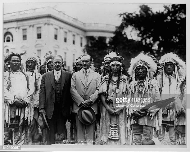 President Calvin Coolidge stands on the South Lawn with Charles H Burke Commissioner of Indian Affairs and members of the Blackfoot tribe Among the...