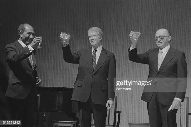 President Cart President Sadat and Prime Minister Begin toast each other following a State Dinner at the White house celebrating the earlier signing...