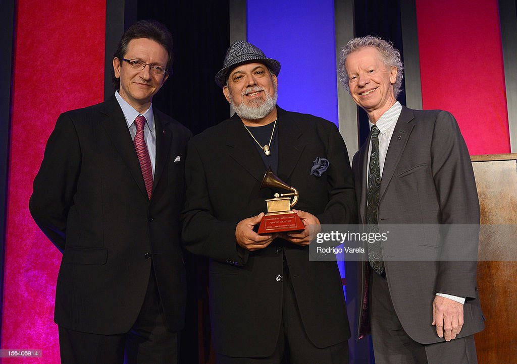 President & CEO of the Latin Academy of Recording Arts & Sciences Gabriel Abaroa Jr. (L) and Trustee of the Latin Recording Academy Terry Lickona (R) present a Lifetime Achievement Award to recording artist Poncho Sanchez (C) at the 2012 Latin Recording Academy Special Awards during the 13th annual Latin GRAMMY Awards at the Four Seasons Hotel on November 14, 2012 in Las Vegas, Nevada.