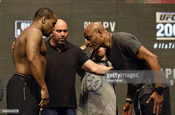 President Dana White looks on as mixed martial artist Anderson Silva bows to mixed martial artist Daniel Cormier during the face off at their weighin...