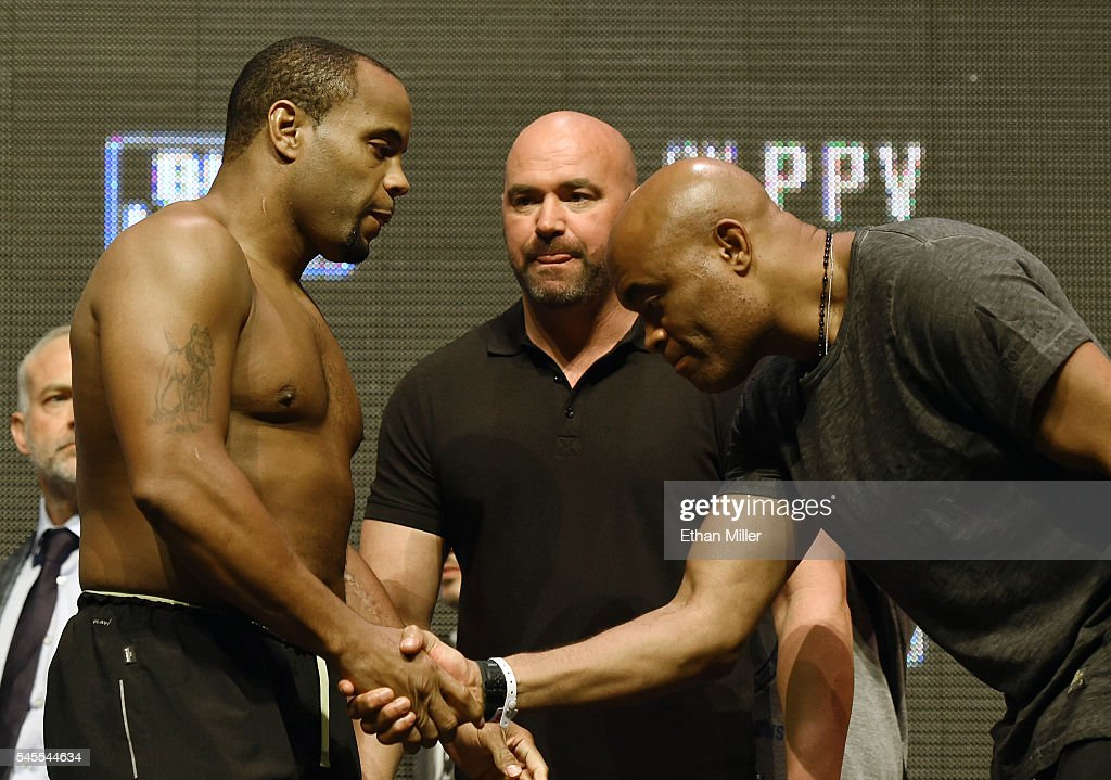 President Dana White looks on as mixed martial artist Anderson Silva shakes hands with and bows to mixed martial artist Daniel Cormier as they face...