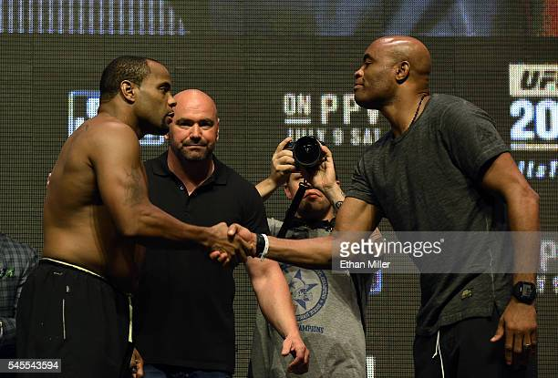 President Dana White looks on as mixed martial artists Daniel Cormier and Anderson Silva shake hands after facing off during their weighin for UFC...