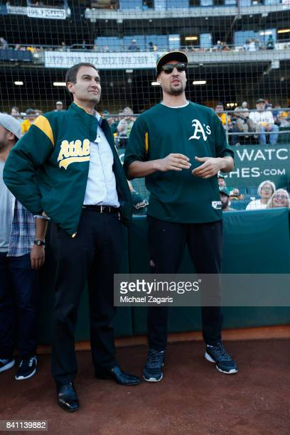 President David Kaval of the Oakland Athletics talks with Klay Thompson of the Golden State Warrios on the field prior to during the game against the...
