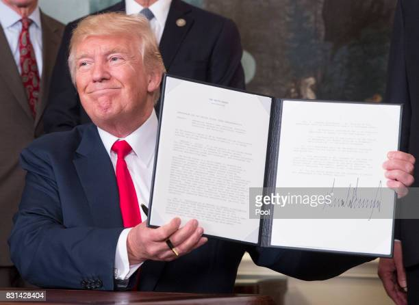 US President Donald J Trump holds a memorandum he just signed on addressing China's laws policies practices and actions related to intellectual...
