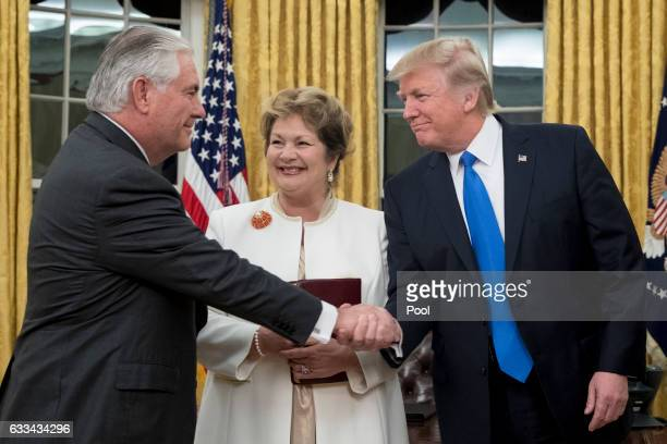 President Donald J Trump shakes hands with Rex Tillerson after Tillerson was swornin as Secretary of State as Tillerson's wife Renda St Clair looks...