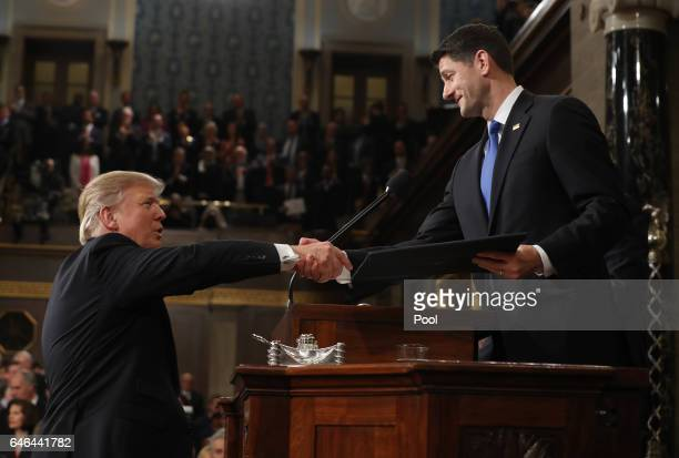 US President Donald J Trump shakes hands with Speaker of the House Paul Ryan as he arrives to deliver an address to a joint session of the US...