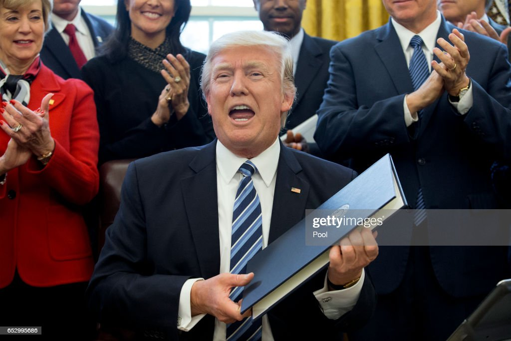 US President Donald J. Trump shows an executive order entitled, 'Comprehensive Plan for Reorganizing the Executive Branch', after signing it beside members of his Cabinet in the Oval Office of the White House on March 13, 2017 in Washington, DC.