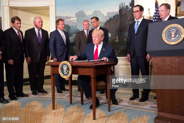 US President Donald J Trump signs a memorandum on addressing China's laws policies practices and actions related to intellectual property innovation...