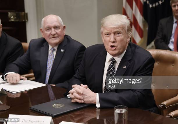 US President Donald speaks as Agriculture Secretary Sonny Perdue looks on during a roundtable with farmers in the Roosevelt Room of the White House...