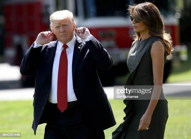 President Donald Trump accompanied by first lady Melania Trump points to his ears as he tries to hear shouted questions from reporters while...