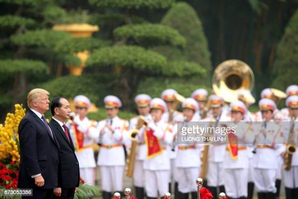 President Donald Trump accompanied by his Vietnamese counterpart Tran Dai Quang observe national anthems during a welcoming ceremony at the...