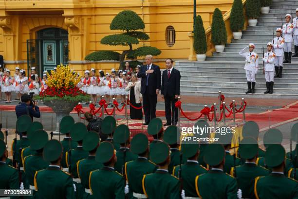 US President Donald Trump accompanied by his Vietnamese counterpart Tran Dai Quang observe national anthems during a welcoming ceremony at the...