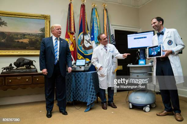 President Donald Trump accompanied by Veterans Affairs Secretary David Shulkin talks with a patient during a Veterans Affairs Department 'telehealth'...
